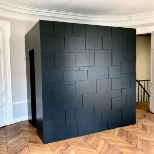 Coffre dressing géométrique noire mat installé comme tête de lit dans une chambre à coucher.