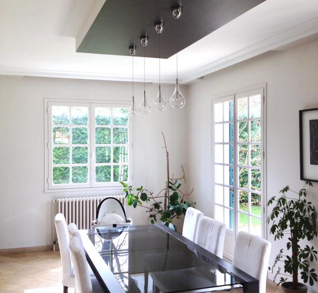 Salle-à-manger moderne, table et chaises sur-mesure, trois lampes en suspensions sur pièce en bois laquée.