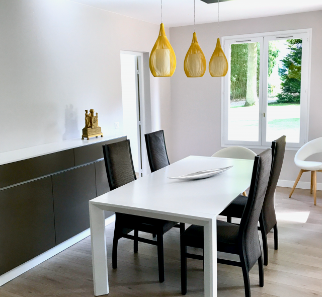 Salle-à-manger lumineuse et moderne avec faux plafond laqué, lampes en suspension jaunes, table, chaises buffet sur mesure, (plateau table silestone blanc).