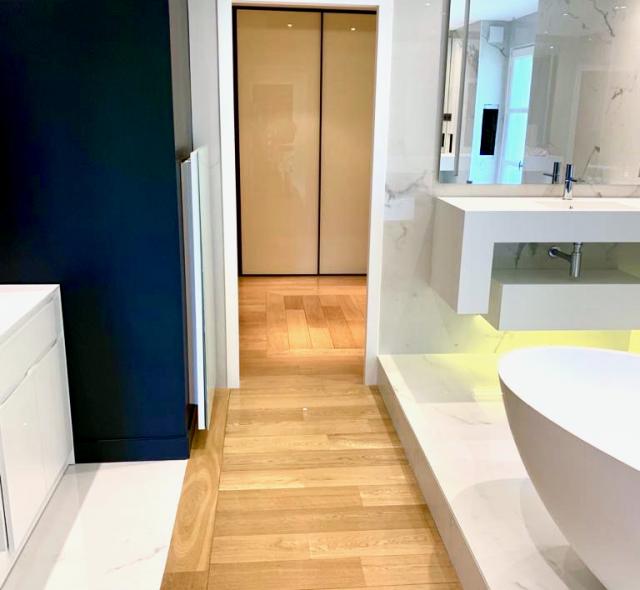 Parquet chêne massif pour dressing avec séparation Mr et Mme. Meuble de salle-de-bains vasque en Corian blanc, miroir éclairé et LED lumineuses - moderne et futuriste.