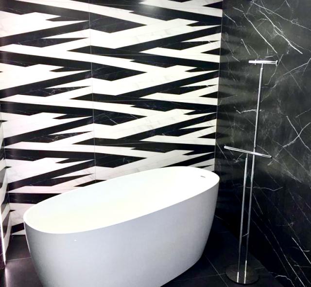 Salle-de-bains monochrome noire et blanche. Baignoire blanche îlot en Corian. Carreaux effet marbre.