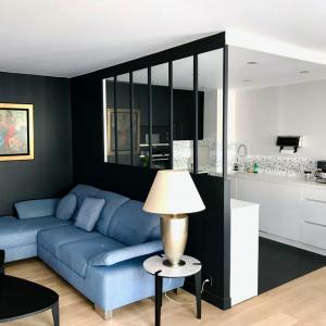 Séjour / salon murs noirs, canapé bleu, verrière de séparation avec la cusine blanche.