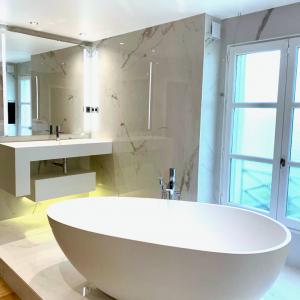 Salle-de-bains moderne et futuriste: baignoire îlot blanche en Corian, céramique effet marbre. Miroir, éclairage coloré LED intégré.